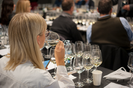 People tasting white wine during a masterclass. Blonde female in the foreground Stock Photo