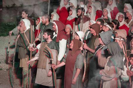 Participantes no identificados durante una recreación histórica. Grupo de campesinos medievales pobres durante un motín.
