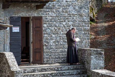 Chiusi della Verna, Arezzo, Italy - 2020, October 30: Monk in prayer near the abbey church.