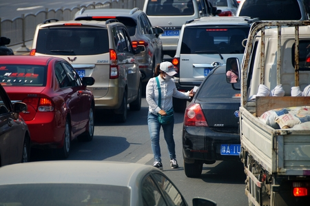 fast lane: On September 15, 2015, Zhengzhou, Henan province, a woman in the fast lane, giving advertising paper to drivers when it was red light at the cross, regardless of security of her own. Editorial