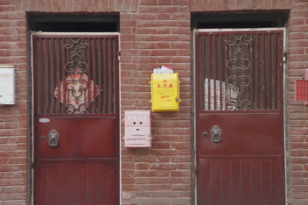 On October 9, 2015, Zhengzhou, Henan,in a residential district, a lot of colorful newspaper boxes, milk cartons were installed on the wall. The red-brick wall seemed very beautiful topped with the colorful boxes. Editorial