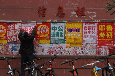 postgraduate: A man pastes a poster for an exam-preparing school at Zhengzhou University in Zhengzhou in central Chinas Henan province Wednesday Nov. 18, 2015. The National Graduate Schools Entrance Exam will be hold on 26 December.