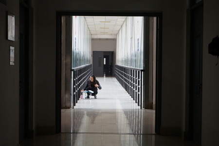 postgraduate: A student studies a material in a aisle of a teaching building at Zhengzhou University in Zhengzhou in central Chinas Henan province Wednesday Nov. 18, 2015. The National Graduate Schools Entrance Exam will be hold on 26 December,2015.