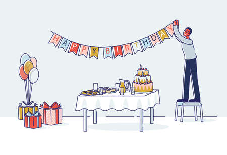 Man decorating room for birthday celebration hanging holiday garland above table with cake