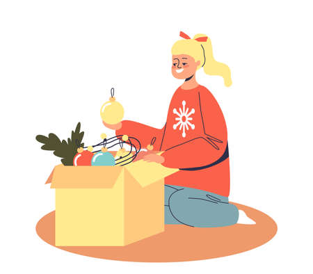 Little girl taking christmas decoration toys for Xmas tree from box preparing for winter holiday