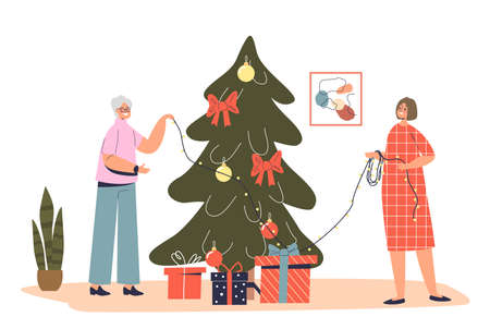Senior lady grandmother decorating christmas tree together with granddaughter