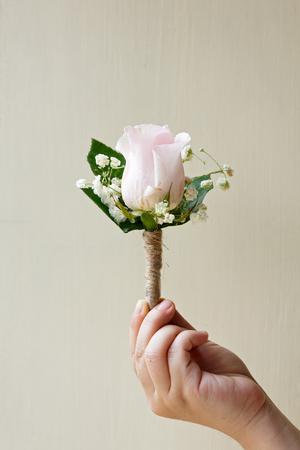 Schließen Sie herauf rosafarbene Rosencorsage in der Hand
