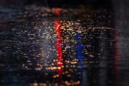 Water reflection on the road with colorful traffic light Фото со стока
