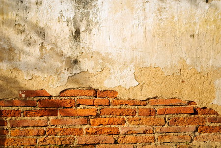 Ancient thai temple cracked brick wall under evening warm sunlight