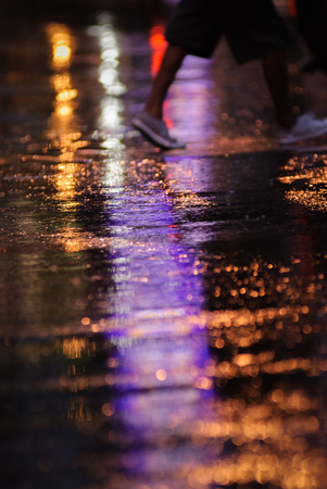 Water reflection on the road with colorful traffic light and walking pedestrian background