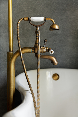 vintage brass douche or faucet at bathtub with grey concrete background