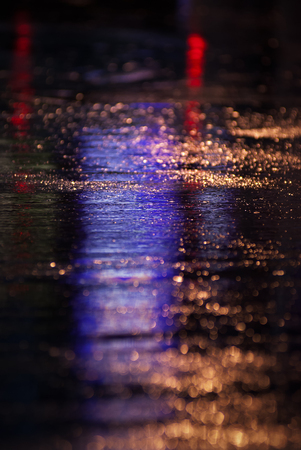 Water reflection on the road with colorful traffic light Stock Photo