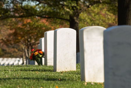 Headstone and bouquet with evening sunlight in autumn at Arlington National Cemetery near to Washington DC Stock Photo