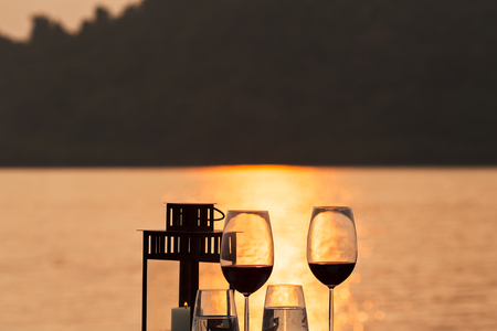 Silhouette of romantic dinner setup at sunset time