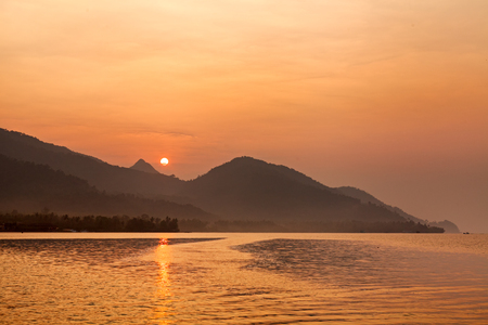 Dramatic scene of sunrise with , sea , mountain , orange sun and boat at ko Chang , Thailand