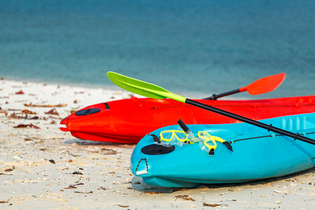 2 Colorful kayaks on beach with green diving mask