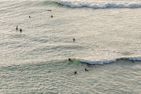 Aerial view of group of surfing under evening sunlight ,Bali ,Indonesia