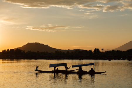 A silhouette scene of tourist Shikara boat in Dal lake with Srinagar fort as a background , Kashmir Stock Photo