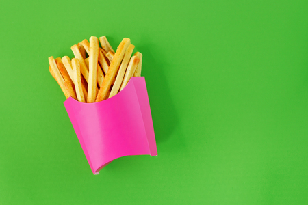 French fries in pink paper box on lime green background Stock Photo