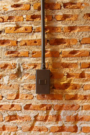 Dark brown light switches on brick wall