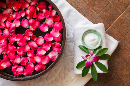 Spa pedicure treatment with foot bath in bowl, red rose petals ,orchid,foot scrub , top view
