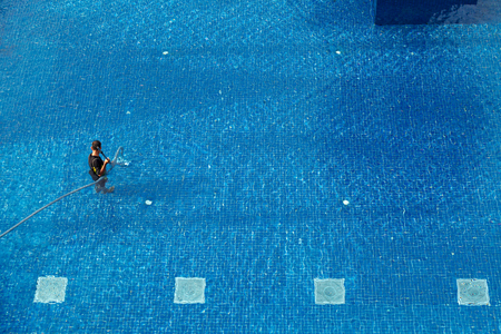 Top view of man in water cleaning swimming pool