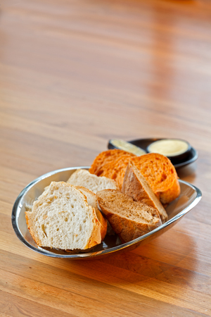 Simply , easy , plain fresh baguette bread slices in plate on wooden table with butter behind