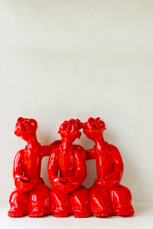 A group of laughing red ceramic doll on white background
