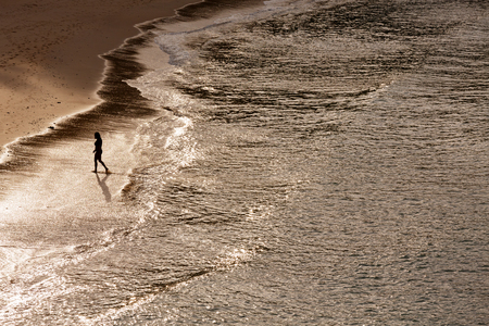 Silhouette of lonely walking woman on the beach with sunlight reflection from aerial view Stock Photo