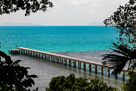 concrete jetty surrounded by the tropical forest with blue ocean , Thailand