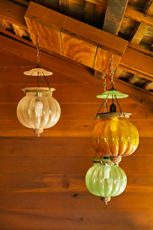 Three asian vintage hanging lamps with wooden wall background