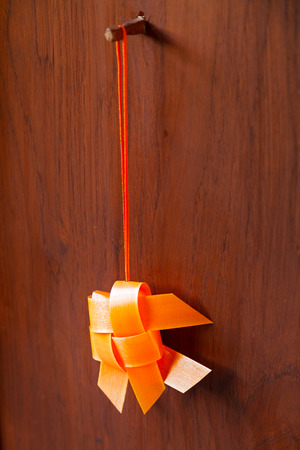 orange thai traditional woven ribbon mobile gold fish hanging on wooden door
