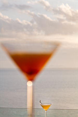 view of two different sizes cocktail comparison under evening sunlight with ocean background