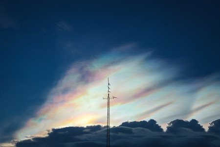 Dramatic silhouette scene of antenna with deep grey cloudy sky with cloud iridescence as a background Stock Photo