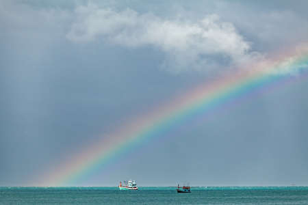 Rainbow overs two fishing boats , Thailand