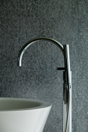 Closeup of modern stainless faucet bathtub with grey background.