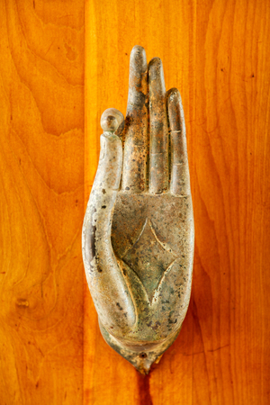 A close up of metal door handle in the shape of image of Buddhas palm on wooden door