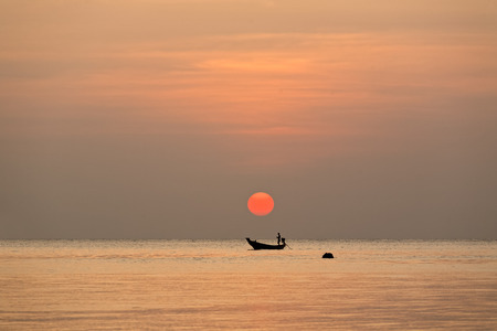 Silhouette of a local fisherman sailing the boat under a big red sundown Stock Photo