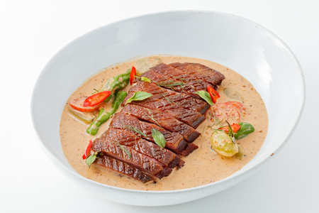 Sliced roasted duck in thai red curry ,Gaeng Ped Yang, with white background