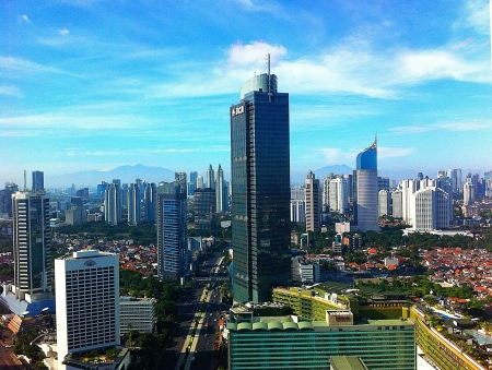 jakarta: Jakarta skyrise building with blue sky and mountain background