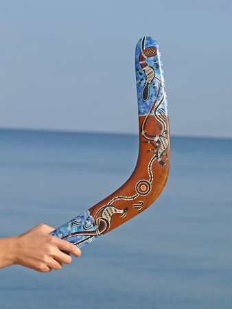 Boomerang in the womens hand against the blue sea. Stock Photo