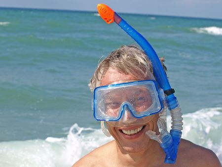 Diver  wearing a mask on the background of the surf.