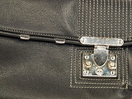Black leather bag with metal lock.  photo