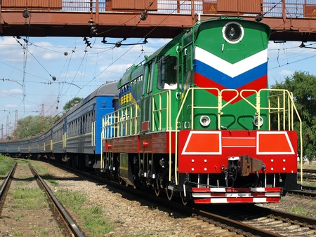 Locomotive and passenger cars under bridge. photo