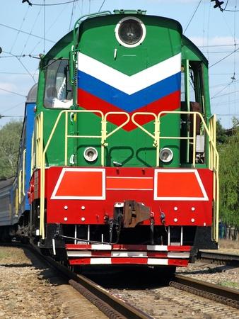 Multicolored locomotive on the rails closeup.