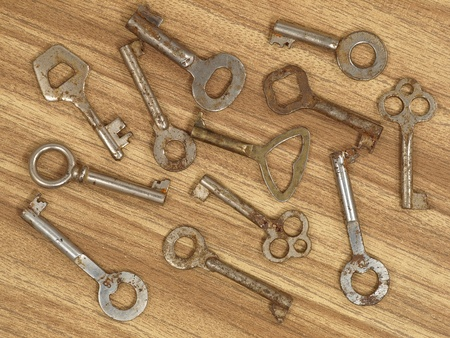 Set of old metal keys on a wooden table background. Stock Photo