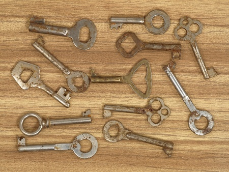 Old metal keys on a wooden table background. photo