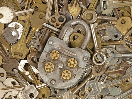 Old lock on a lot metal keys background.