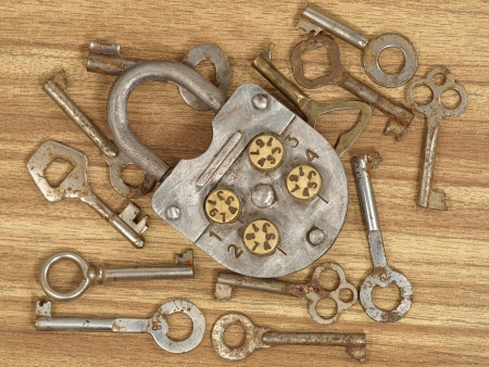 Old metal lock and keys on a wooden table background. photo