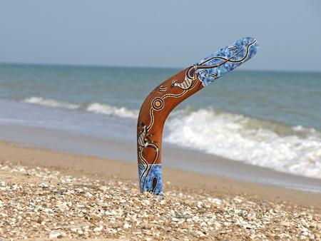 Boomerang on Sandy Beach Against of Sea Surf.